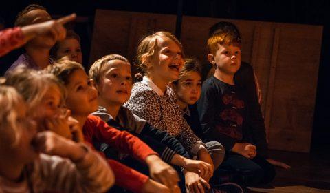Lachende kinderen kijkend naar de voorstelling